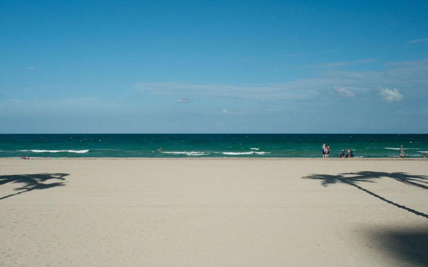 Tourists on beach against sky