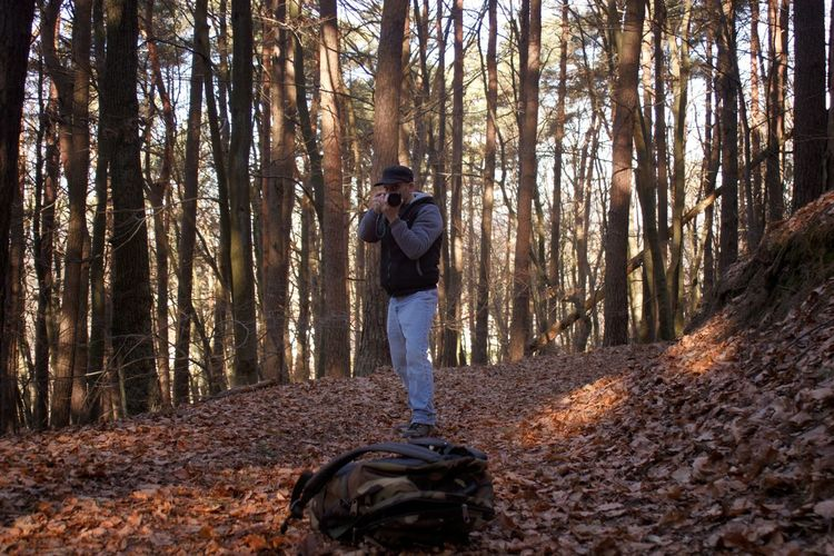 Man photographing with camera against trees in forest