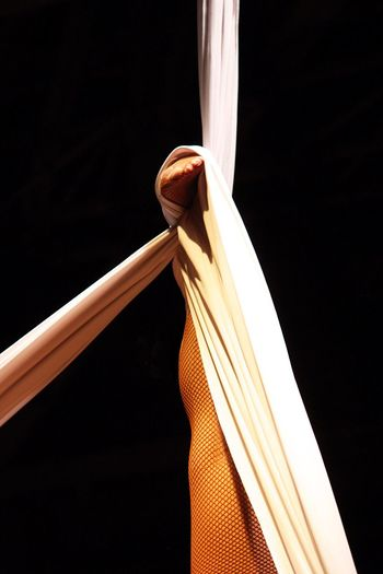 Low section of woman performing aerial silk against black background