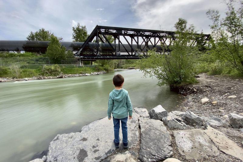 Rear view of boy standing on bridge