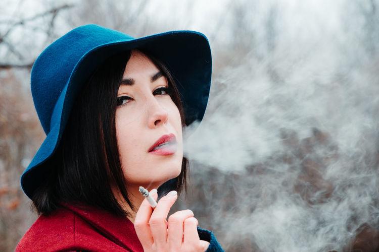 Portrait of beautiful young woman wearing hat smoking cigarette