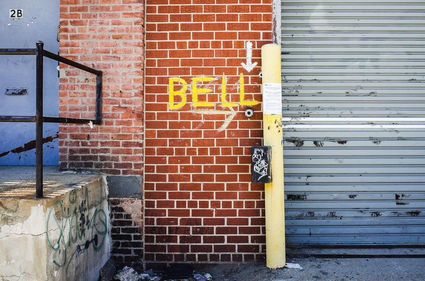 Big Bell Sign Architecture Brick Wall Built Structure Cracks Day Information Sign No People Outdoors Pole Text Textures And Surfaces Wall - Building Feature