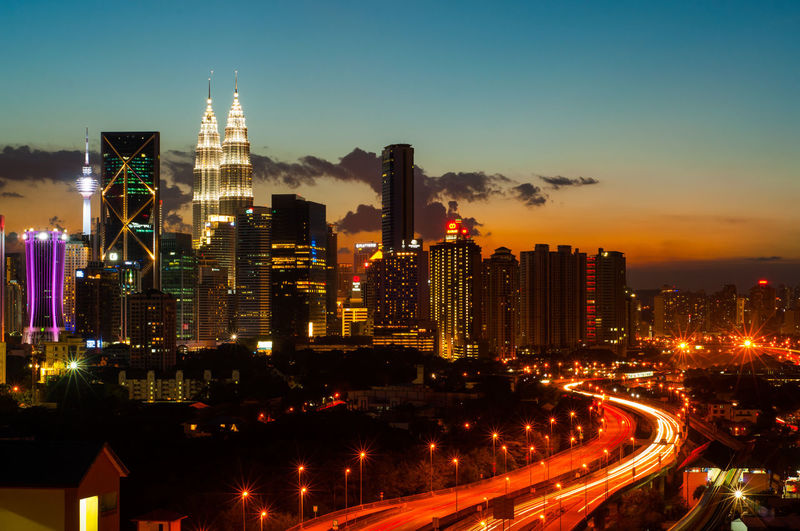 Light trails on two lane highway leading towards petronas tower