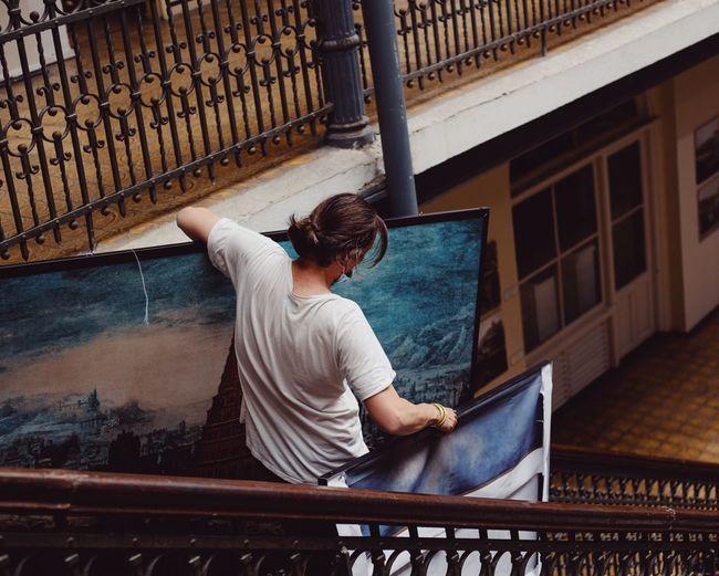 Man standing on railing by window