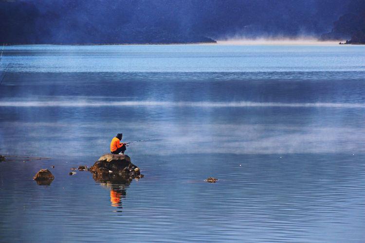 Man fishing in lake while sitting on rock