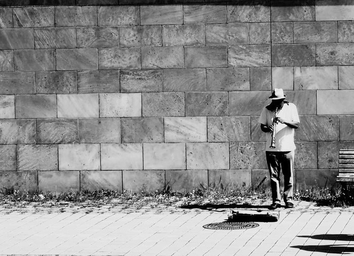 Berlin busker by the riverside Saxophone Blackandwhite Photography Blackandwhite Busker One Person Real People Standing Day Wall - Building Feature Shadow Sunlight Men