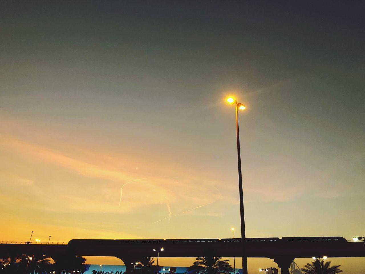 sky, street light, sunset, street, lighting equipment, illuminated, nature, bridge, architecture, bridge - man made structure, low angle view, outdoors, built structure, connection, silhouette, no people, transportation, car, cloud - sky, motor vehicle, light