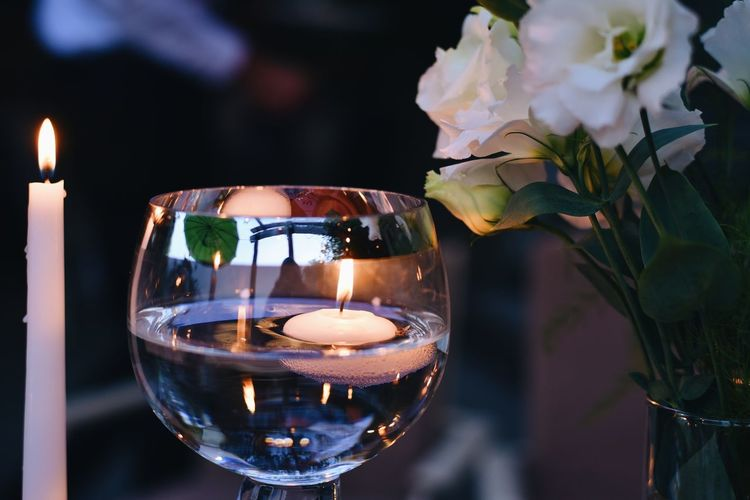 Close-up of lit candles on glass table