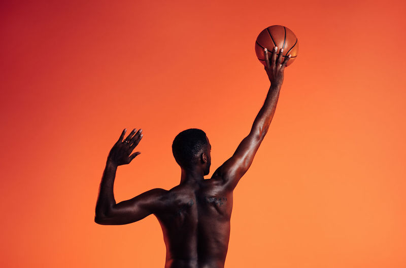 Rear view of shirtless man with arms raised against orange background