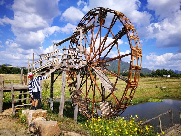 Boy standing by water wheel at farm