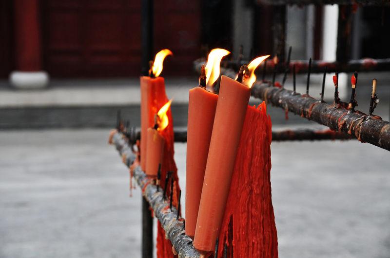 Orange Candles Burning On Metal Sticks