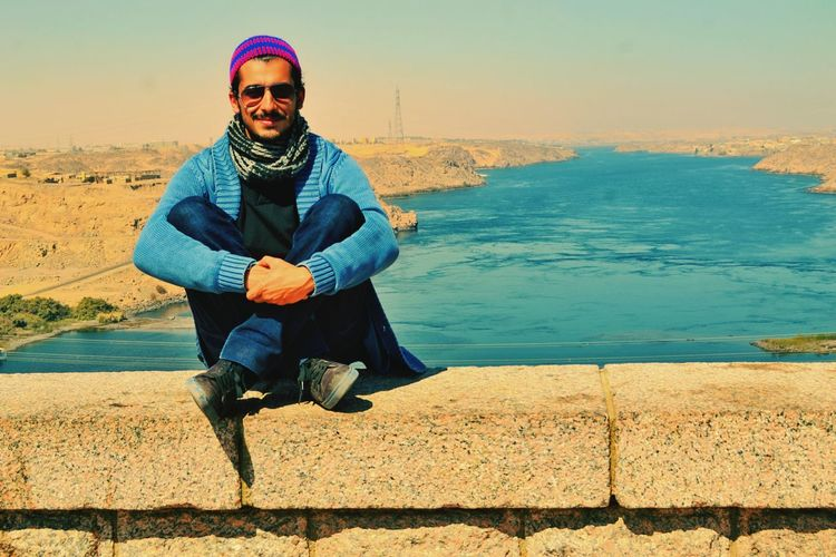 Portrait of young man sitting on retaining wall against nile river