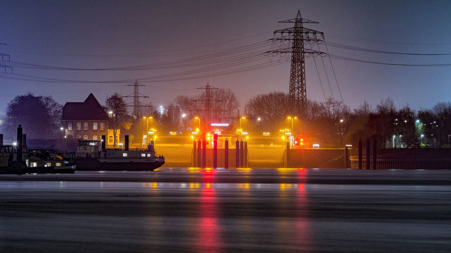 Boats Moored At River Against Electricity Pylons At Dusk