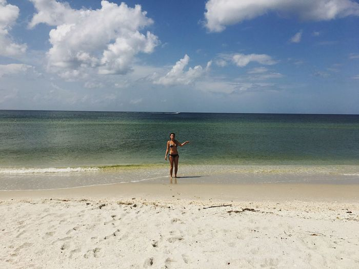 Woman in bikini standing on shore at beach against sky
