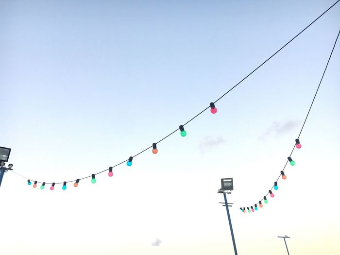 Low Angle View Of Colorful Light Bulbs Hanging Against Sky