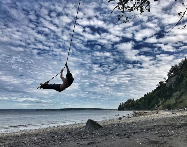Low angle view of man swinging on rope over beach against cloudy sky