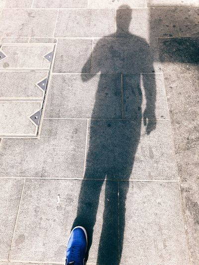 Low section of person standing on shadow