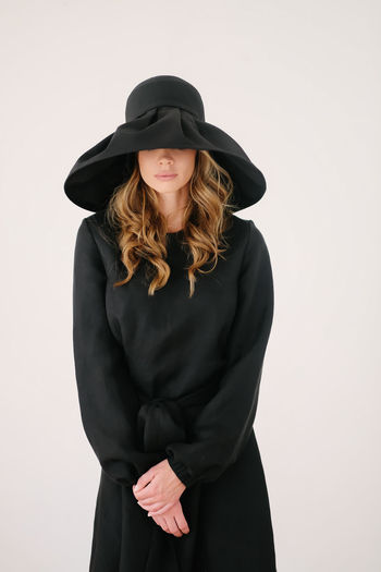 Young woman wearing hat standing against white background