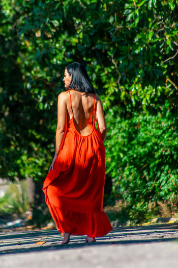 Rear view of female model standing on road at park