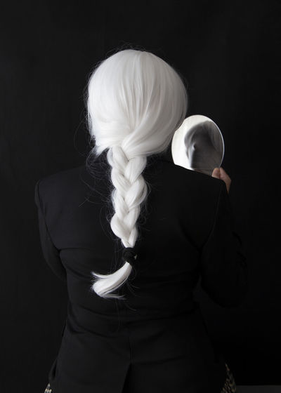 Rear view of woman holding mirror while standing against black background