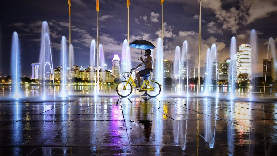 Man Cycling By Illuminated Fountain In City At Night