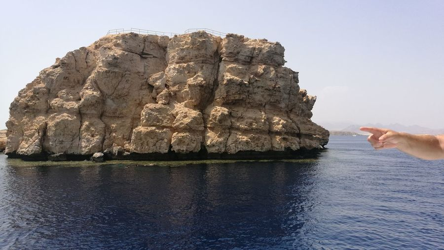 Person on rock formation against sea against clear sky