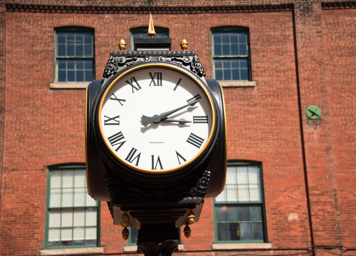 Vintage black street clock in front of building