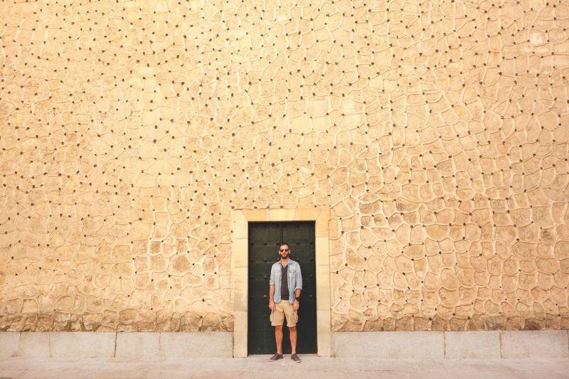 Man standing against closed door of old building