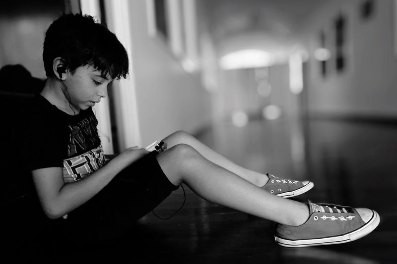 Side view of boy sitting at home