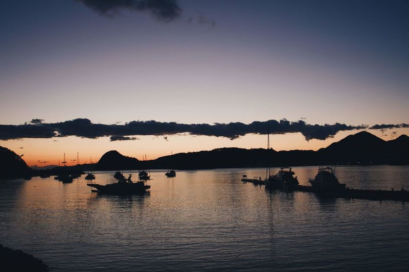 Silhouette boats in lake against sky during sunset