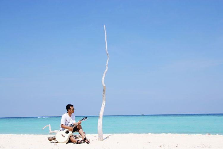 Man playing guitar sitting at beach against sky