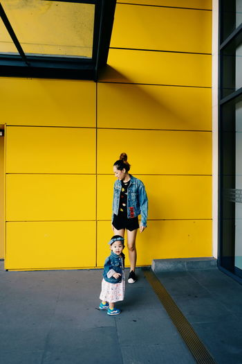 Mother with cute daughter standing against building