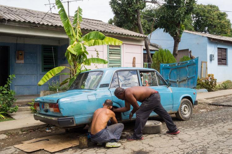 Repairing an old Soviet car in a Cuban street Blackandwhite Cuban Street Scenar Day Land Vehicle Mecanicien Mode Of Transport Old Car Parked Repairs Soviet Car The Street Photographer - 2016 EyeEm Awards Tree Vintage Cars