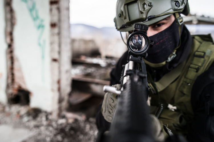 Portrait of sniper aiming rifle while standing outdoors