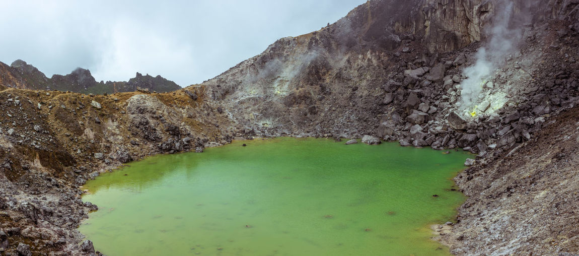 Panorama of a Rain water lake in a volcano crater with escaping sulphur gases, Mount Sibayak, Sumatra, Indonesia. Berastagi Cloud - Sky Crater Crater Edge Crater Lake Eruption Exploring Explosion INDONESIA Lake Mount Sibayak Panorama Southeast Asia Sulphur Sulphur Gas Sumatra  Trekking Volcanic Landscape Volcanic Rock Volcano Volcano Crater