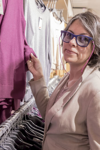 Side view portrait of woman shopping in clothes store