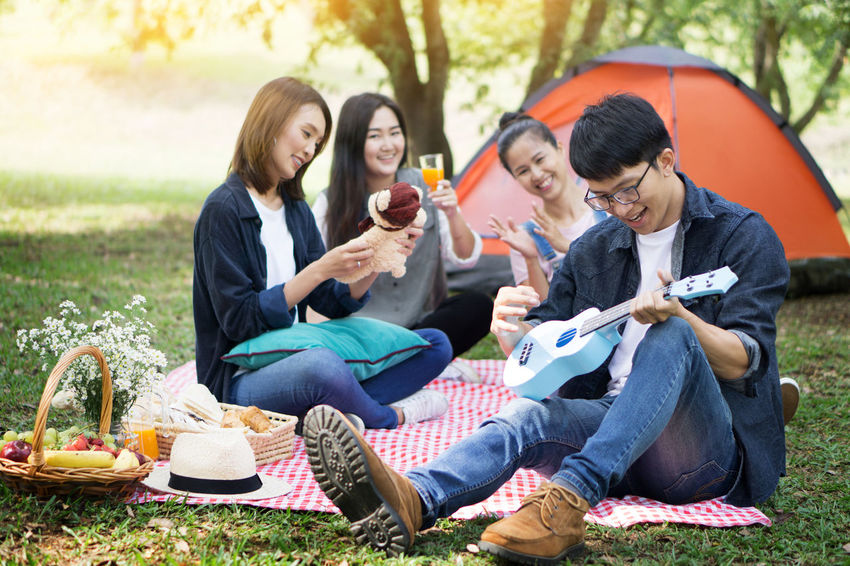 Casual Clothing Day Drink Food And Drink Friendship Full Length Grass Holding Lawn Leisure Activity Mid Adult Mid Adult Women Outdoors Park - Man Made Space Picnic Picnic Basket Picnic Blanket Refreshment Relaxation Sitting Smiling Togetherness Tree Women Young Women