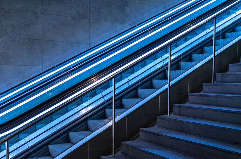 Underground Futuristic Neon Lights Technology Blue Diagonal Lines Best Of Stairways Railing Staircase Steps And Staircases Architecture Built Structure No People Modern Indoors  Pattern Low Angle View Day Glass - Material Escalator Absence Building Empty
