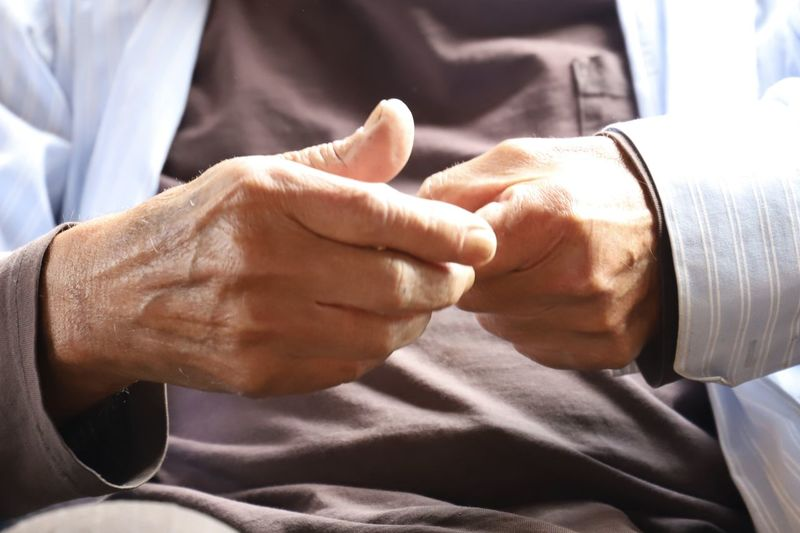 Midsection of senior man fist bumping with doctor in hospital