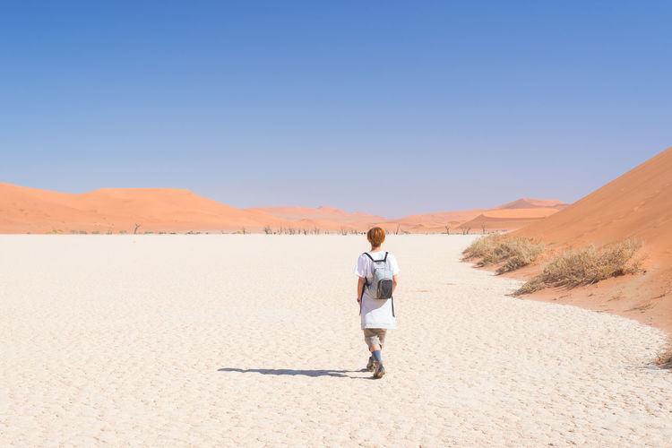 Rear view of mature woman walking at desert against sky