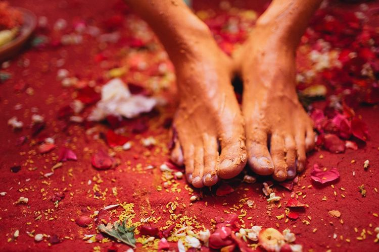 Close-up of bride with turmeric on feet during haldi