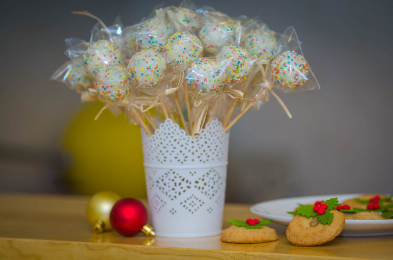 Close-Up Of Sweet Food With Baubles On Table