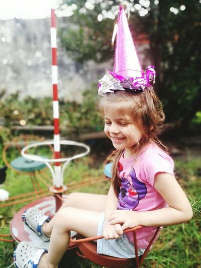 Happy girl wearing party hat while sitting on chair in yard