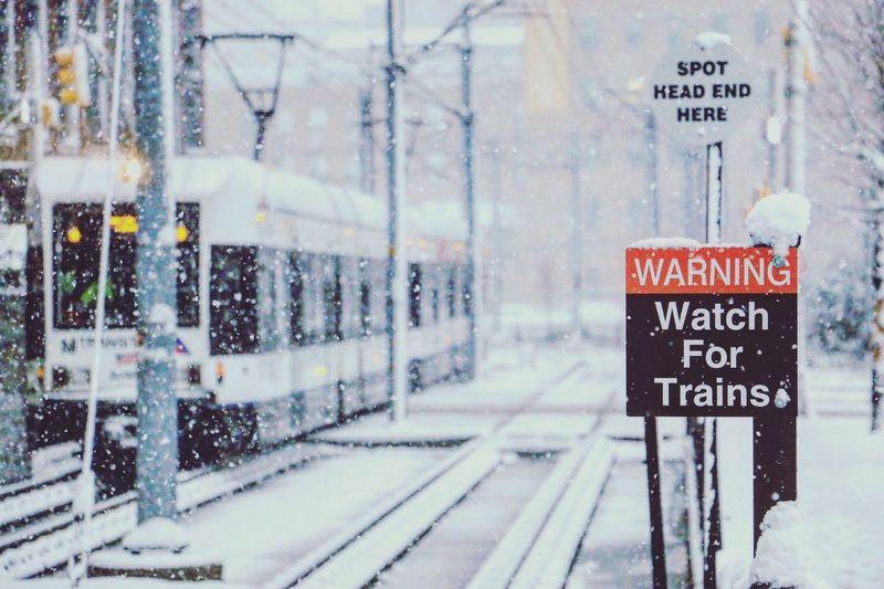 Warning sign by railroad tracks during snowfall