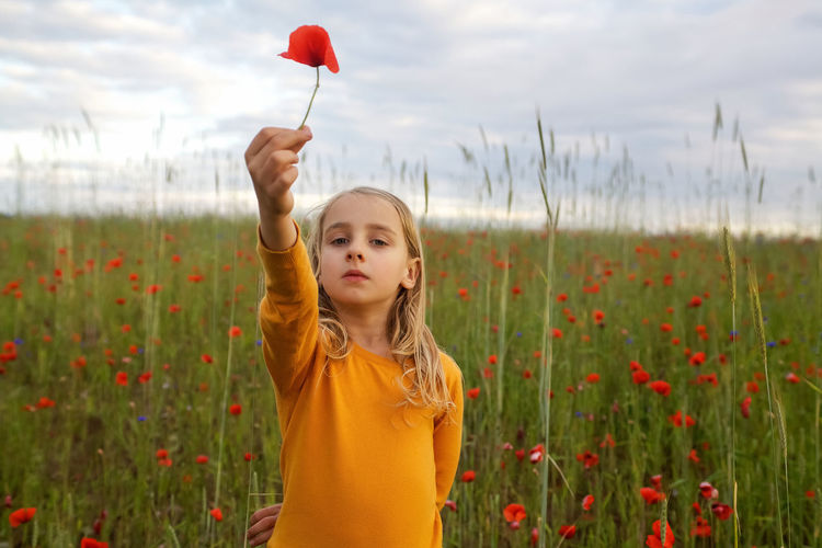 Portrait Of Girl Holding Red Flower While Standing On Field