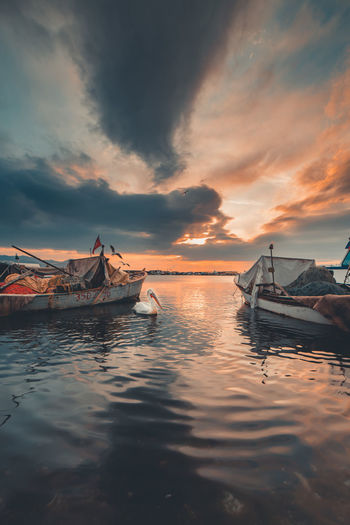 Fishing boats in sea against sky during sunset