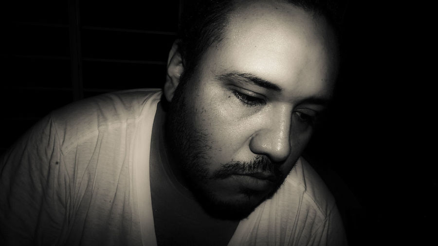Close-up of thoughtful man looking down against black background
