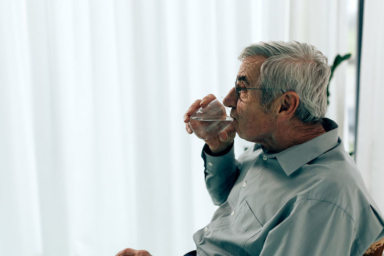Side view of a man drinking glass