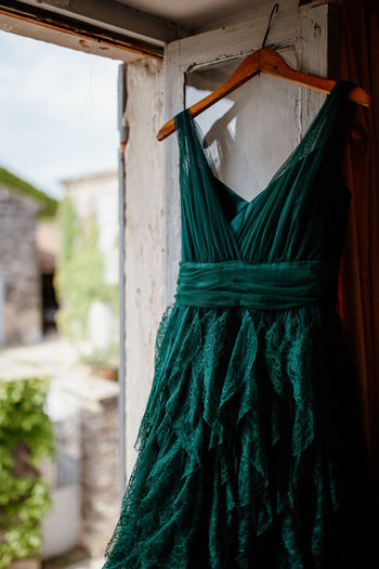 Green dress hanging on window at home