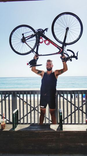 Warrior On Wheels Over Head Bicycle Lifting Up Water Sky Sea One Person Real People Men Full Length Nature Standing Lifestyles Leisure Activity Transportation Horizon Over Water Horizon Front View Casual Clothing Beach Outdoors Day Mature Men
